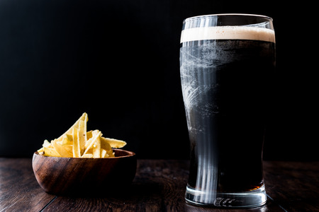 Dark Beer with snacks potato chips on wooden surface. Beverage Concept.