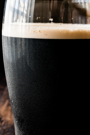 Dark Beer on wooden surface. Close up view. Beverage Concept.