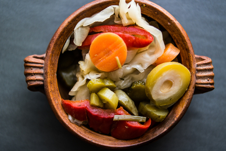 Mix of Turkish Pickles with green tomatoes, red pepper, cucumber and carrot in a bowl.