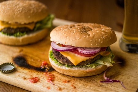 A hamburger (or cheeseburger when served with a slice of cheese) is a sandwich consisting of one or more cooked patties of ground meat, usually beef, placed inside a sliced bread roll or bun.