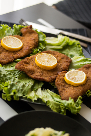 Schnitzel serve with greens and lemon