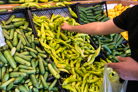 man is buying green peppers at greengrocer