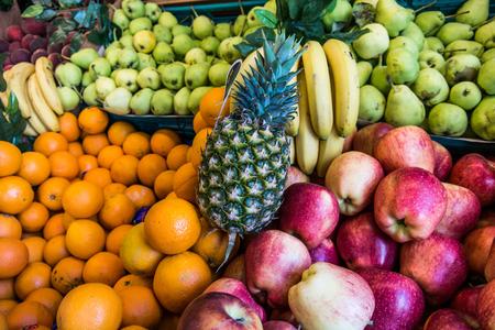 pineapple, oranges, apples and bananas at greengrocer.