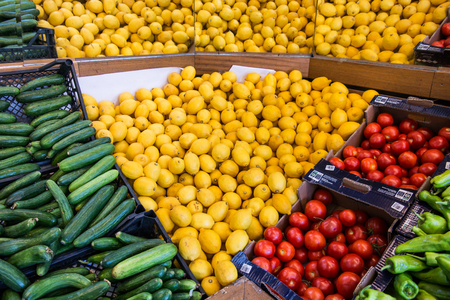 fresh melons, cucumbers, tomatoes and green peppers at supermarket or greengrocer / greengrocery