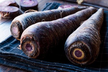 Purple Carrots on Dark Wooden Surface. Organic Food.