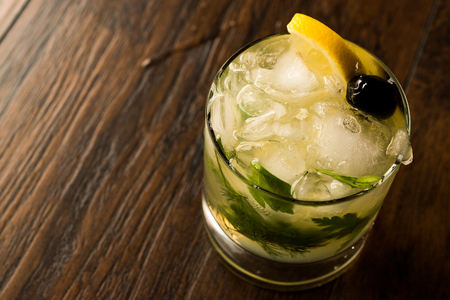 Dillionaire Cocktail with Dill, Gin, Parsley, lemon, Olive and Crushed Ice. Beverage Concept. Stock Photo