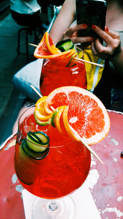 Spritz Cocktail with cucumber and red orange on a red table. Summer Concept.