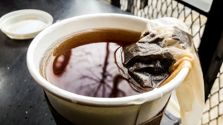Tea Bag in paper or plastic coffee cup fast food concept. Stock Photo