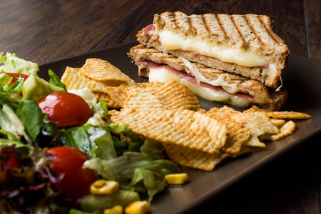 Turkish Toast or Tost  Triangle Club Sandwich with Melted Cheese, Ham and Served with Chips and Salad. Fast Food. Stock Photo