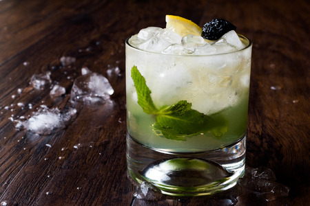 Whiskey Smash Cocktail with Mint Leaves, Lemon, Olive and Crushed Ice. Beverage Concept.