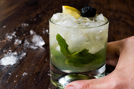 Whiskey Smash Cocktail with Mint Leaves, Lemon, Olive and Crushed Ice. Served with Barman Hand. Beverage Concept. Stock Photo