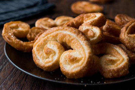 Palmier Cookies in Black Plate on Wooden Surface. Dessert Concept.