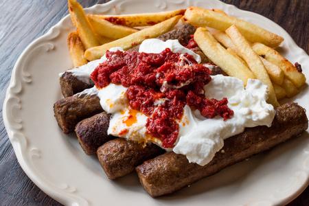 Balkan Cevapcici Kofta / Kofte Kebab with Yogurt, Tomato Sauce and Potatoes. Traditional Food. Foto de archivo - 96991906
