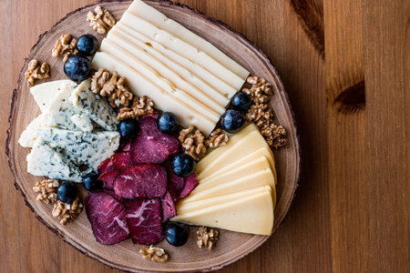 Cheese Plate with smoked meat, walnuts and grapes on wooden surface. Organic Food. Banco de Imagens