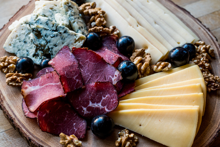Cheese Plate with smoked meat, walnuts and grapes on wooden surface. Organic Food. 写真素材