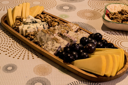 Cheese plate: Emmental, Camembert cheese, blue cheese, cheddar, grape, walnuts on wooen surface