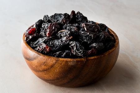 Organic Dried Raw Raisins in Wooden Bowl. Organic Food.