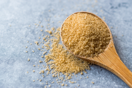 Brown Sugar in Wooden Spoon with Package. Organic Food. Stock Photo