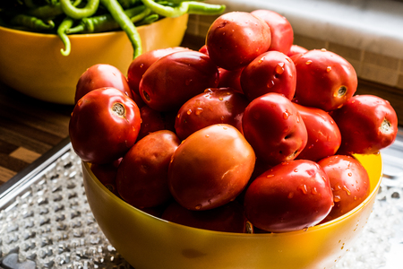 Tomatoes in yellow bowl at kitchen. Organic food Concept. Stock Photo