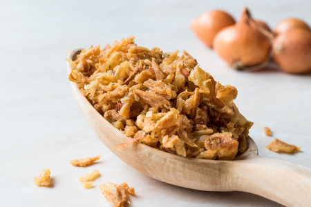 Fried Crispy Onion Flakes with Wooden Spoon. Organic Food.