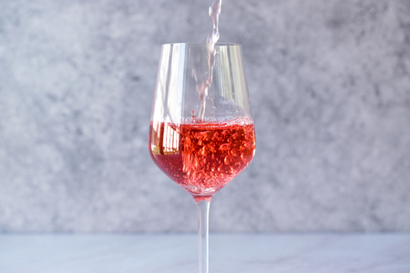 Pouring Pink Rose Blush Wine to Glass. Beverage Concept.