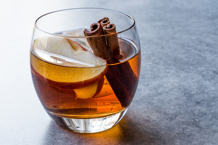 Apple Cider Whiskey Cocktail with Cinnamon Sticks, Ice and Apple Slices. Beverage Concept.
