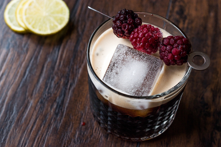 Black  Dark Beer Cocktail with Blackberries and Ice on Wooden Surface. Beverage Concept.