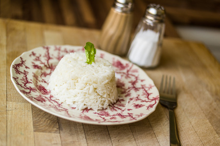pilaf served with plate on wooden surface