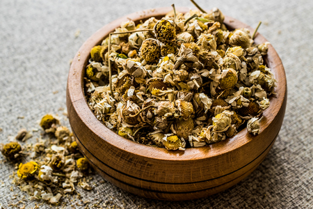 Dried Camomile flower tea in wooden bowl (papatya-bobune). Organic Concept.