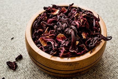 Dried hibiscus flowers in wooden bowl. Organic Concept.