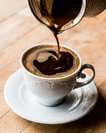 Pouring Turkish Coffee into the cup. Traditional Beverage.