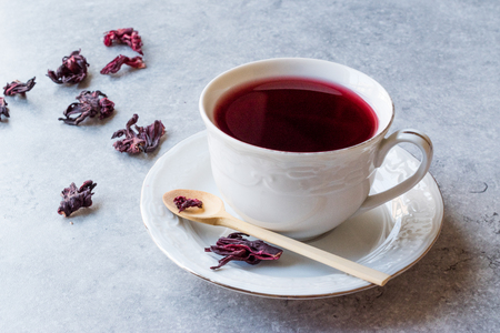 Red Hot Hibiscus Tea in White Cup with Dried Hibiscus Tea Leaves. Organic Beverage Stock Photo