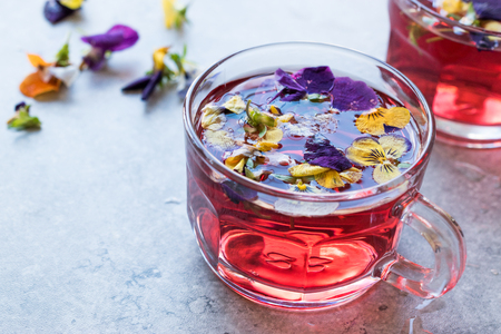 Red Herbal Tea with Edible Flowers. Organic Beverage.