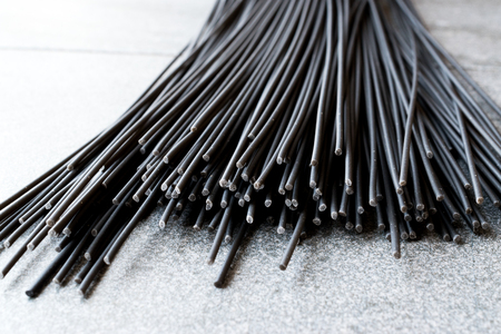Raw Black Spaghetti Pasta Flavored with Squid ink or Cuttlefish. Organic Food.