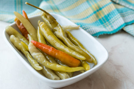 Pickled Green Pepper Pickles in Bowls. Traditional Organic Food.