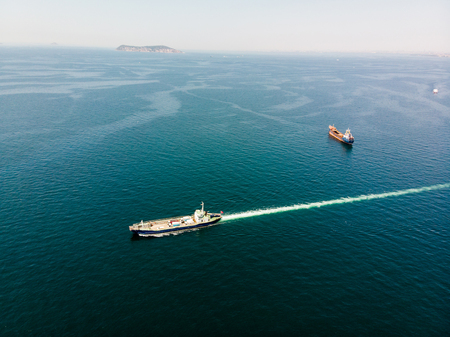 Aerial Drone View of Cargo Ship Carry Vehicles to the Island. Transportation 版權商用圖片