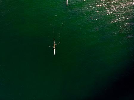 Luftdrohnenansicht des Ruderteams mit Kanu in ruhiger See- / Vogelperspektive. Sport in der Natur Standard-Bild