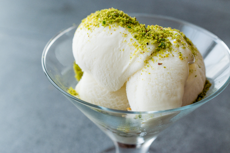 Turkish Maras Vanilla Ice Cream with Pistachio Powder Served Portion in Glass Cup. Traditional Organic Summer Dessert.