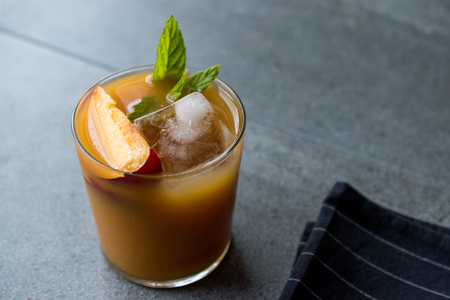 Peach Bourbon Cocktail with Peach Slice, Mint Leaves and Ice. Summer Beverage.