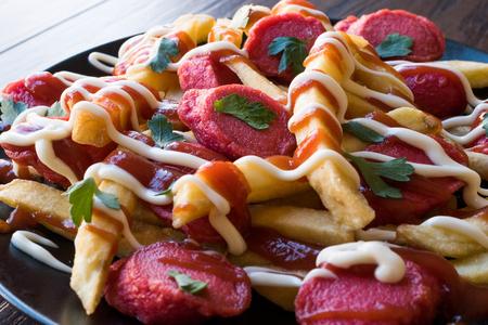 Homemade Peruvian Salchipapa Fries with Sausage Slices, Ketchup and Mayonnaise. Traditional Food. 写真素材