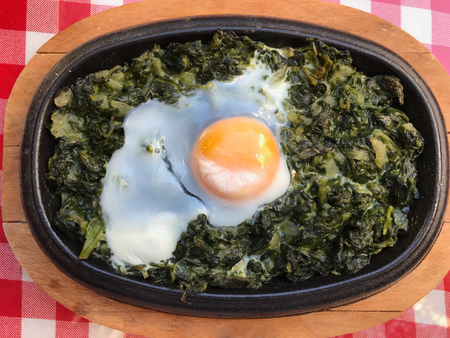 Casserole Spinach with Egg on Red Tablecloth and Wooden Surface. Traditional Organic Food.