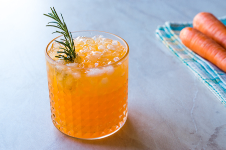 Carrot Cocktail with Crushed Ice and Rosemary. Beverage Concept.