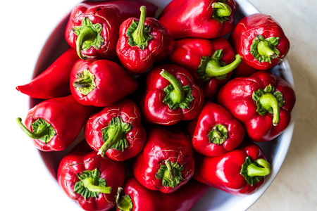 Whole Red Peppers in White Bowl. Close Up View. Organic Food.