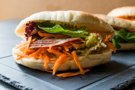 Taiwan's Pita Bread Bun Sandwich Gua Bao with Smoked Bacon, Carrot Slices and Greens from Asia. Traditional Organic Food.