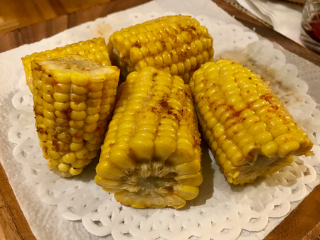 Homemade Grilled and Buttered Golden Corn Cobs with Butter, Red Pepper Powders and Black Pepper. Organic Food. Stock Photo