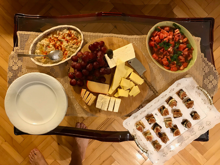Homemade Appetizer Table with Cheese Plate, Hummus, Fig Canepe with Tomato Salad. Party Table.