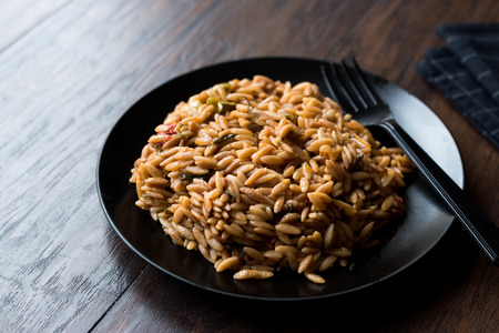 Turkish Style Cooked Orzo Pasta in Black Plate  Pilav or Pilaf. Organic Food.