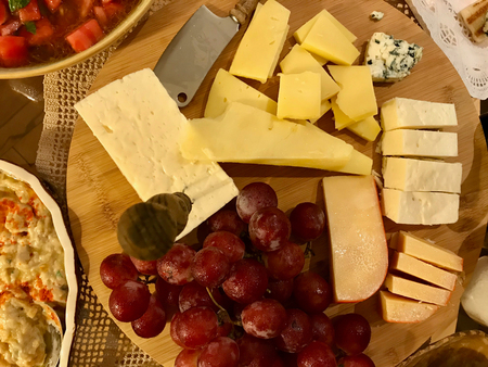 Cheese Plate with Grapes on Round Wooden Surface. Organic Appetizer.