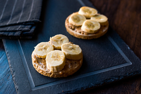 Bulgur Rice Cakes with Sliced Bananas and Peanut Butter  Round Crackers. Organic Healthy Snacks.