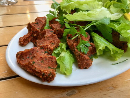 Turkish Food Cig Kofte with lettuce and parsley in plate. Traditional Food.